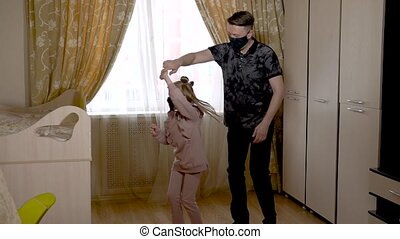 Enjoying old dad dancing with a beautiful little girl in a large living room in fashionable clothes. On against a bright window. They are masked