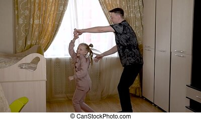 Enjoying old dad dancing with a lovely little girl in a large living room in home clothes. On against a bright window.