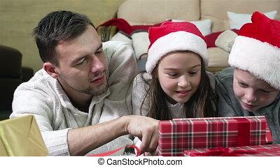 Enjoying Presents - Parents and children enjoying Christmas...