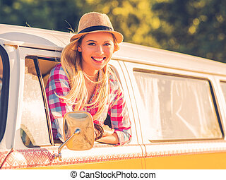 Enjoying road trip. Beautiful young woman looking at camera and smiling while looking through the vehicle window