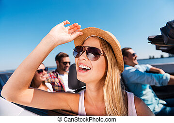 Enjoying road trip. Group of young happy people enjoying road trip in their convertible while beautiful woman adjusting her hat and smiling