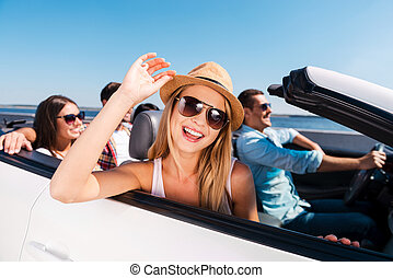 Enjoying road trip. Group of young happy people enjoying road trip in their white convertible