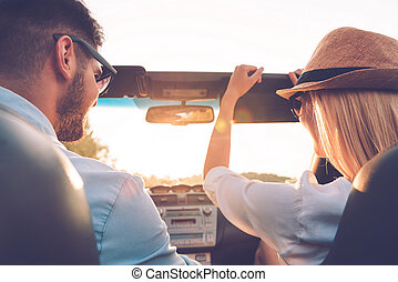 Enjoying road trip together. Rear view of joyful young couple having fun while riding in their convertible