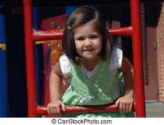 Enjoying School Recess - Little girl hangs between the rungs...