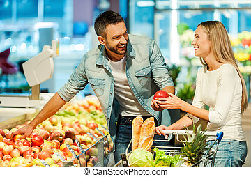 Enjoying shopping together. Beautiful young smiling couple choosing apples in supermarket together