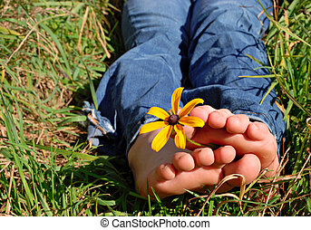 Barefoot girl holding a flower between her toes outside in the grass
