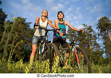 Couple of cyclers on their bikes in the countryside on hot summer day