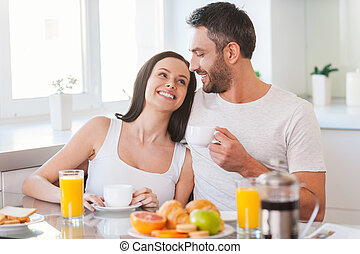 Enjoying Sunday morning together. Beautiful young couple bonding to each other and smiling while sitting in the kitchen together and having breakfast