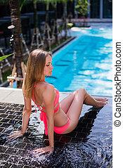 Enjoying suntan. Pretty young woman in bikini sitting near swimming pool.