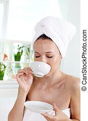 Enjoying tea - Vertical shot of young woman enjoying tea in...