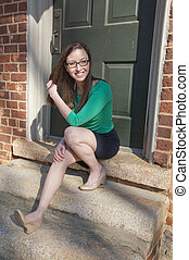 A young woman sitting outside on a stoop enjoying a sunny afternoon