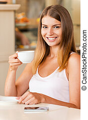 Enjoying the best coffee in town. Attractive young woman drinking coffee and smiling while sitting in coffee shop