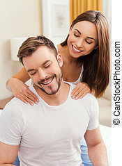 Enjoying the best massage. Beautiful young loving couple sitting together in bed while woman massaging her boyfriend