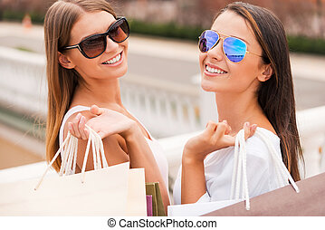 Enjoying the day shopping. Rear view of two beautiful young women holding shopping bags and looking over shoulder with smile while standing outdoors