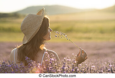 Enjoying the fragrance - Beautiful young woman with a straw ...