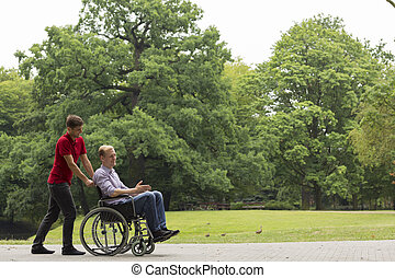Shot of a young man and his friend in a wheelchair having a walk in a park