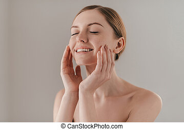 Enjoying the softness of her skin. Studio portrait of attractive woman with freckles on face touching her skin and keeping eyes closed while standing against background