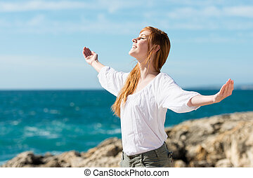 A pretty happy young woman enjoying the sun stands with her arms outspread against an ocean backdrop