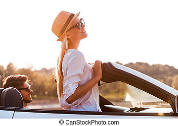 Enjoying the sun and fresh air. Side view of cheerful young woman leaning at the wind shield while her boyfriend sitting near on front seat of convertible