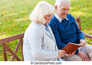 Enjoying their favorite book together. Cheerful senior couple reading a book together while sitting on the park bench