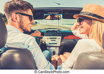 Enjoying their road trip. Side view of cheerful young couple holding hands and looking at each other while sitting inside of their convertible