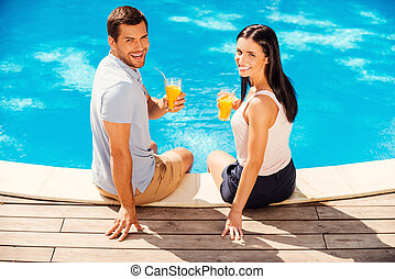 Enjoying their summer vacation. Top view of happy couple in casual wear holding glasses with orange juice and smiling while sitting poolside together