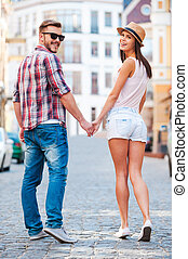 Enjoying their time together. Rear view of beautiful young loving couple walking by the street and looking over shoulder