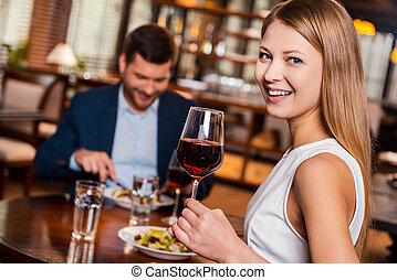 Enjoying time together. Beautiful young woman holding glass with red wine and smiling while sitting at the restaurant with her boyfriend sitting in the background