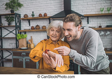 Good-looking elderly lady in yellow feeling great with her son