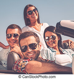 Enjoying time together. Group of young happy people enjoying road trip in their white convertible