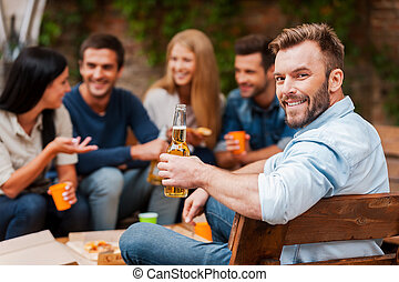 Enjoying time with friends. Happy young man holding bottle with beer and looking at camera while his friends talking to each other in the background