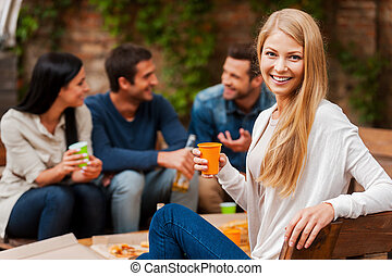 Enjoying time with friends. Smiling young woman holding glass and looking at camera while her friends talking to each other in the background
