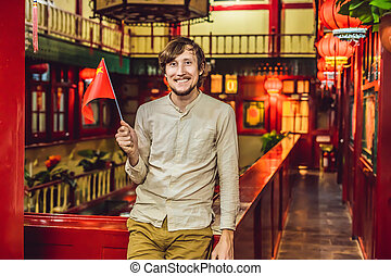Enjoying vacation in China. Young man with a Chinese flag on a Chinese background. Travel to China concept. Visa free transit 72 hours, 144 hours in China BANNER, LONG FORMAT