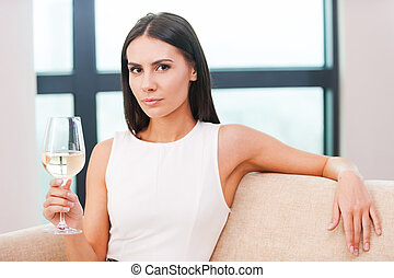 Enjoying white wine. Beautiful young blond hair woman in evening gown sitting on the couch and holding glass with white wine