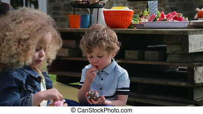 Enjoyiong a Chocolate Cupcake - Little boy and his friend...