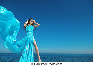 Enjoyment. Fashion model woman with blowing dress over blue...