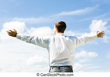 Image of businessman standing aback and looking at blue sky in summer