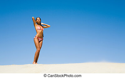 Enjoyment - Photo of young luxurious woman standing on sandy...