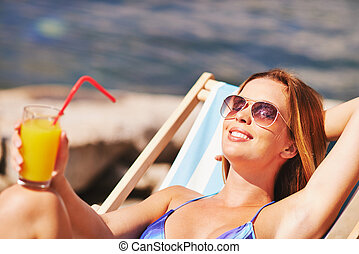 Enjoyment - Restful young woman with juice sunbathing on...