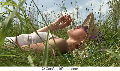 enjoyment   - Young woman lying on grass