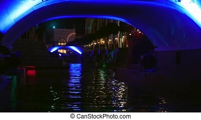 Enlightened bridge over canal - People walks along canal in...