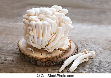 Enoki mushrooms on wooden background, close up.