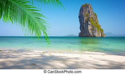 Enormous Rock Jutting from Tropical Sea near Sandy Beach