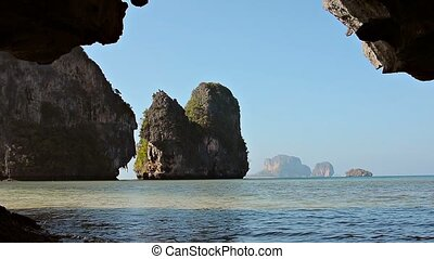 Enormous Rocks on a Tropical Coastline from inside a Cave -...