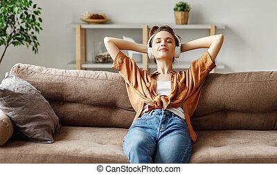 enquanto, escutar, agradado, sofá, jovem, relaxante, música, fones, mulher, lar