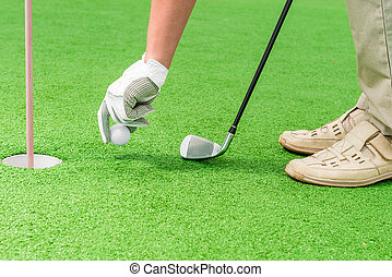 en's hand in a glove putting a golf ball near the hole