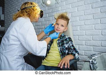 Ent doctor or Otolaryngologist examining a kid ear