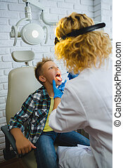 Ent doctor or Otolaryngologist examining a kid throat