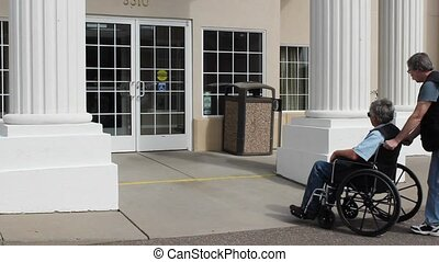 entering a rehab clinic - A disabled man in a wheelchair is...