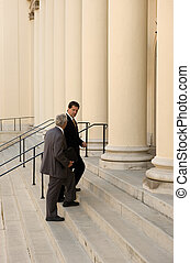 Entering Court - Attorney and client walking up the steps of...